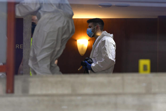 Forensic workers collect body parts and evidence from a hotel downtown Bucharest, Romania, Friday, June 19, 2020. Gholamreza Mansouri, a former judge from Iran sought by his country to face corruption charges has died after falling from a high floor inside a hotel. Romanian police said only that a man had fallen from a high floor at a hotel in Bucharest, the Romanian capital, and was found dead. (AP Photo/Andreea Alexandru)