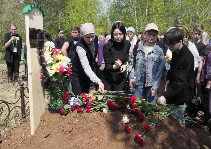 People lay flowers at the grave of Elvira Ignatieva, an English language teacher, who was killed at a school shooting on Tuesday in Kazan, Russia, Wednesday, May 12, 2021. Russian officials say a gunman attacked a school in the city of Kazan and Russian officials say several people have been killed. Officials said the dead in Tuesday's shooting include students, a teacher and a school worker. Authorities also say over 20 others have been hospitalised with wounds. (AP Photo/Dmitri Lovetsky)