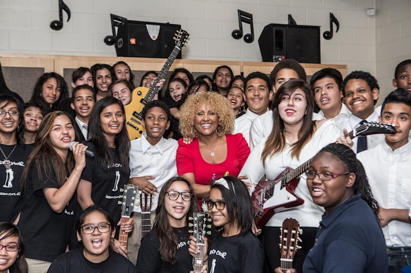 In this June 5th, 2013 photo provided by Little Kids Rock, Darlene Love poses with students at Franklin L. Williams Middle School in Jersey City, N.J., where Love delivered instruments and jammed with the children. On Thursday night,Oct. 17, 2013, fellow Rock and Roll Hall of Fame members honored Love at a New York City benefit for Little Kids Rock, which provides musical instruments and lessons for budget-strapped schools.(AP Photo/Little Kids Rock)