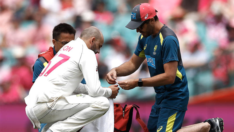 Nathan Lyon gets treatment from Australian Team Physiotherapist David Beakley after he injured his thumb while fielding off his own bowling during day three of the Third Test match. (Photo by Ryan Pierse/Getty Images)