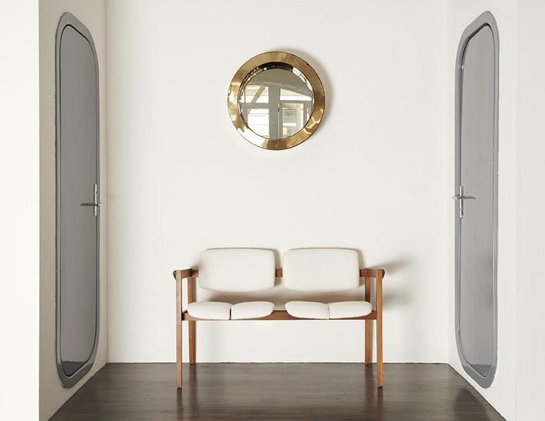 A Finn Juhl bench in an alcove between children's bedrooms, whose doors are a 1967 Charlotte Perriand design, inside a New York residence on Wooster Street.