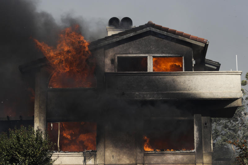 Flames rise as a home is consumed by a wildfire Tuesday, Dec. 5, 2017, in Ventura, Calif. (AP Photo/Jae C. Hong)