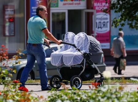 A man with a baby carriage walks in a park, central Bakhmut