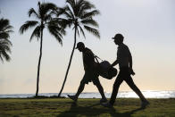 Joaquin Niemann, right, of Chile, walks from the 11th green with caddie Gary Matthews during the second round of the Sony Open golf tournament Friday, Jan. 15, 2021, at Waialae Country Club in Honolulu. (AP Photo/Jamm Aquino)