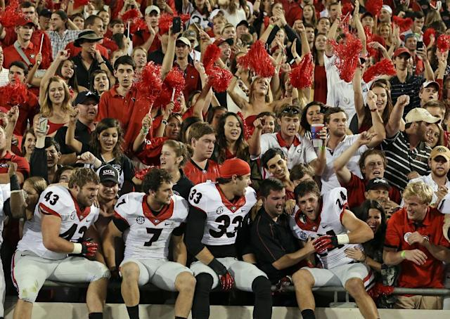Georgia players Merritt Hall (43), Blake Sailors (7), Chase Vasser (33), and Lucas Redd (24) celebrate with fans after their 23-20 win over Florida in an NCAA football game, Saturday, Nov. 2, 2013, in Jacksonville, Fla. (AP Photo/John Raoux)