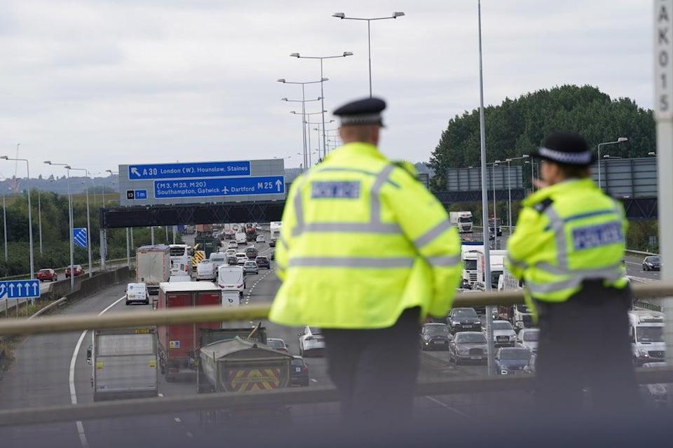 Police officers watch the M25 motorway near Heathrow Airport for Insulate Britain protestors (Steve Parsons/PA) (PA Wire)
