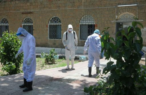 Yemeni medical workers disinfect their hazmat suits outside a quarantine centre for COVID-19 patients in Yemen's third city of Taez on June 21