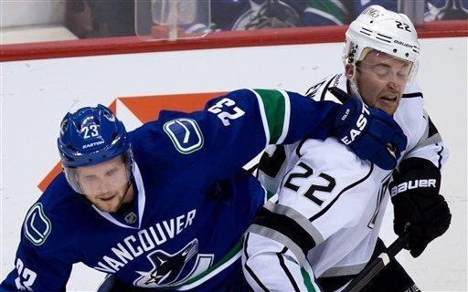 Vancouver Canucks' Alexander Edler, left, of Sweden, and Los Angeles Kings' Trevor Lewis collide during the second period of an NHL hockey game in Vancouver, British Columbia on Saturday, March 2, 2013. (AP Photo/The Canadian Press, Darryl Dyck)