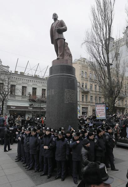 FILE - In this Sunday Dec. 1, 2013 file photo, police guard the monument of Vladimir Lenin in Kiev, Ukraine. Anti-government protesters have toppled the statue of Bolshevik leader Vladimir Lenin in central Kiev amid huge protests gripping Ukraine. A group of protesters dragged down and decapitated the landmark statue Sunday, Dec. 8, 2013 after hundreds of thousands of others took to the streets to denounce the government's move away from Europe and toward Moscow. (AP Photo/Efrem Lukatsky, File)