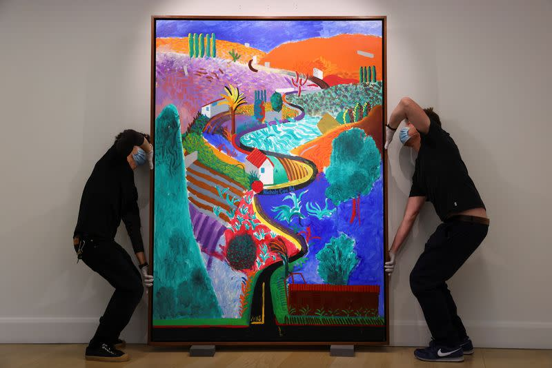 Employees adjust a painting by David Hockney entitled 'Nichols Canyon' which has an estimated value of $35 million at Phillips auction house in London