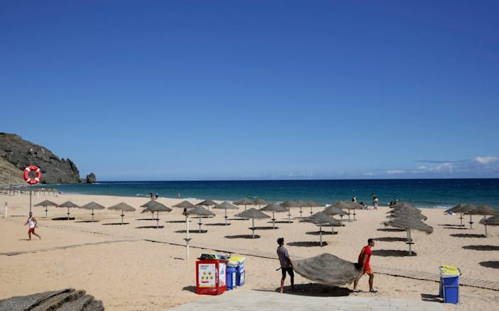 Two men set up sun umbrellas at the beach in Praia da Luz, in Portugal's Algarve coast - Armando Franca/AP