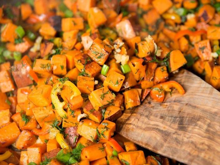 chopped sweet potato and wooden spoon