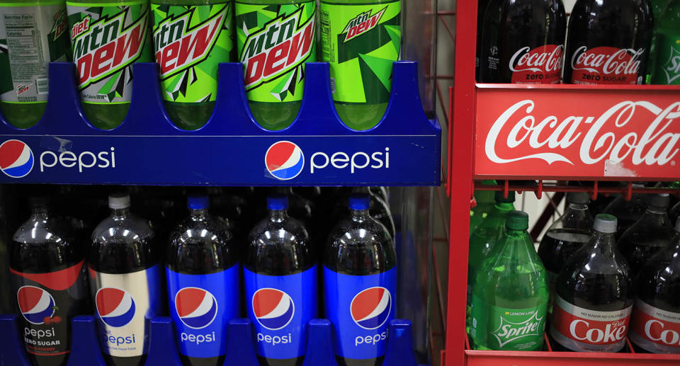 Bottles of Pepsi and Mountain Dew soda for sale next to Coca-Cola Co. brand beverages.