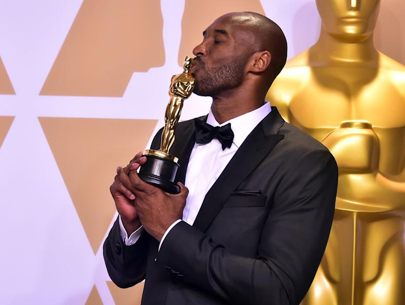 "TOPSHOT - Kobe Bryant poses in the press room with the Oscar for Best Animated Short Film for ""Dear Basketball,"" during the 90th Annual Academy Awards on March 4, 2018, in Hollywood, California. (Photo by FREDERIC J. BROWN / AFP) (Photo credit should read FREDERIC J. BROWN/AFP via Getty Images)"