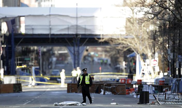 A officials stands guard in front of the Boston Marathon finish line, Thursday, April 18, 2013, in Boston. President Barack Obama plans to attend a service honoring the victims Thursday in Boston, where police were stationed on street corners across downtown. (AP Photo/Julio Cortez)