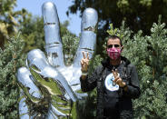 """Musician Ringo Starr poses in front of his """"Peace and Love"""" public sculpture on his 80th birthday, Tuesday, July 7, 2020, in Beverly Hills, Calif. (AP Photo/Chris Pizzello)"""