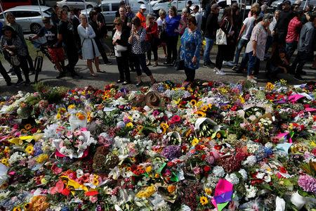 People visit a memorial site for victims of Friday's shooting, in front of Christchurch Botanic Gardens in Christchurch, New Zealand March 19, 2019. REUTERS/Jorge Silva