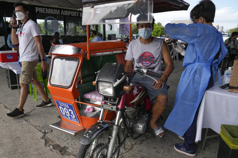 A pedicab driver is inoculated with China's Sinovac COVID-19 Vaccine in Manila, Philippines on Tuesday, June 22, 2021, in Manila, Philippines. The Philippine president has threatened to order the arrest of Filipinos who refuse the COVID-19 vaccination and told them to leave the country for hard-hit countries like India and the United States if they would not cooperate with massive efforts to end the pandemic. (AP Photo/Aaron Favila)