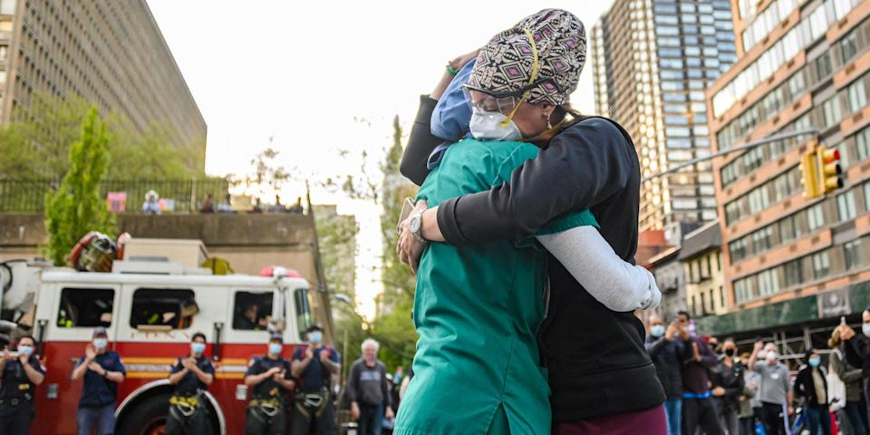 Medical workers hug outside NYU Langone Health hospital as people applaud to show their gratitude to medical staff and essential workers during the coronavirus pandemic on May 7, 2020 in New York City.
