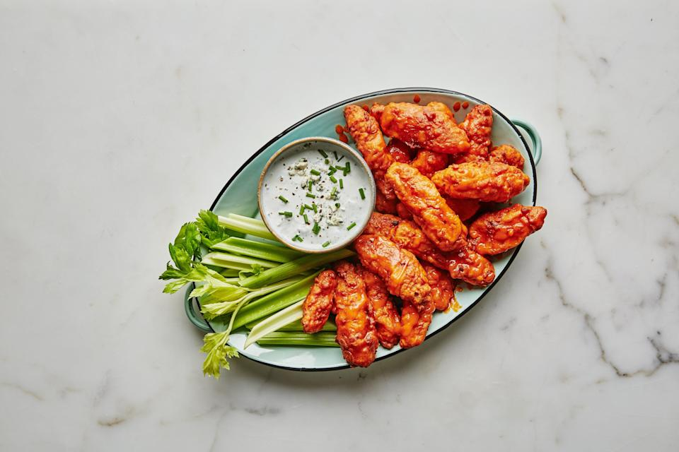 "Let's be honest: No one is into Buffalo chicken wings for the bones. So skip the hassle and make spicy fried chicken breast strips instead. Pair them with a tangy blue cheese dip and crunchy celery sticks. <a href=""https://www.epicurious.com/recipes/food/views/boneless-buffalo-chicken-wings?mbid=synd_yahoo_rss"" rel=""nofollow noopener"" target=""_blank"" data-ylk=""slk:See recipe."" class=""link rapid-noclick-resp"">See recipe.</a>"