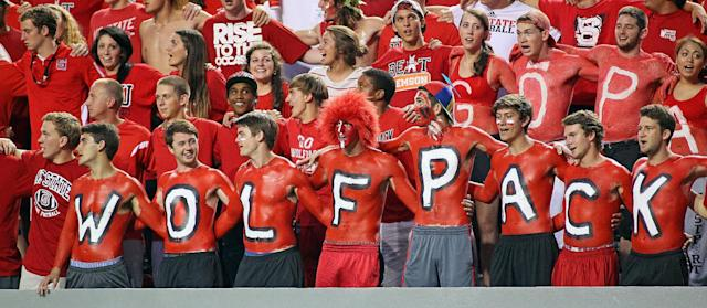 North Carolina State fans don body paint during the first half of an NCAA college football game against Clemson, in Raleigh, N.C., Thursday, Sept. 19, 2013. Clemson won 26-14. (AP Photo/Karl B DeBlaker)