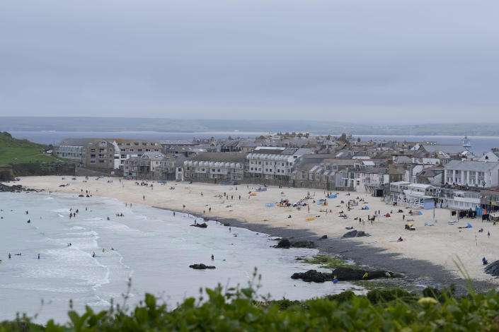 Surfers and sunbathers enjoy the beach at St. Ives, Cornwall, England, Thursday, June 10, 2021. G7 leaders and guests will meet in the the Cornish resort of Carbis Bay starting Friday, June 11, 2021. (AP Photo/Alastair Grant)