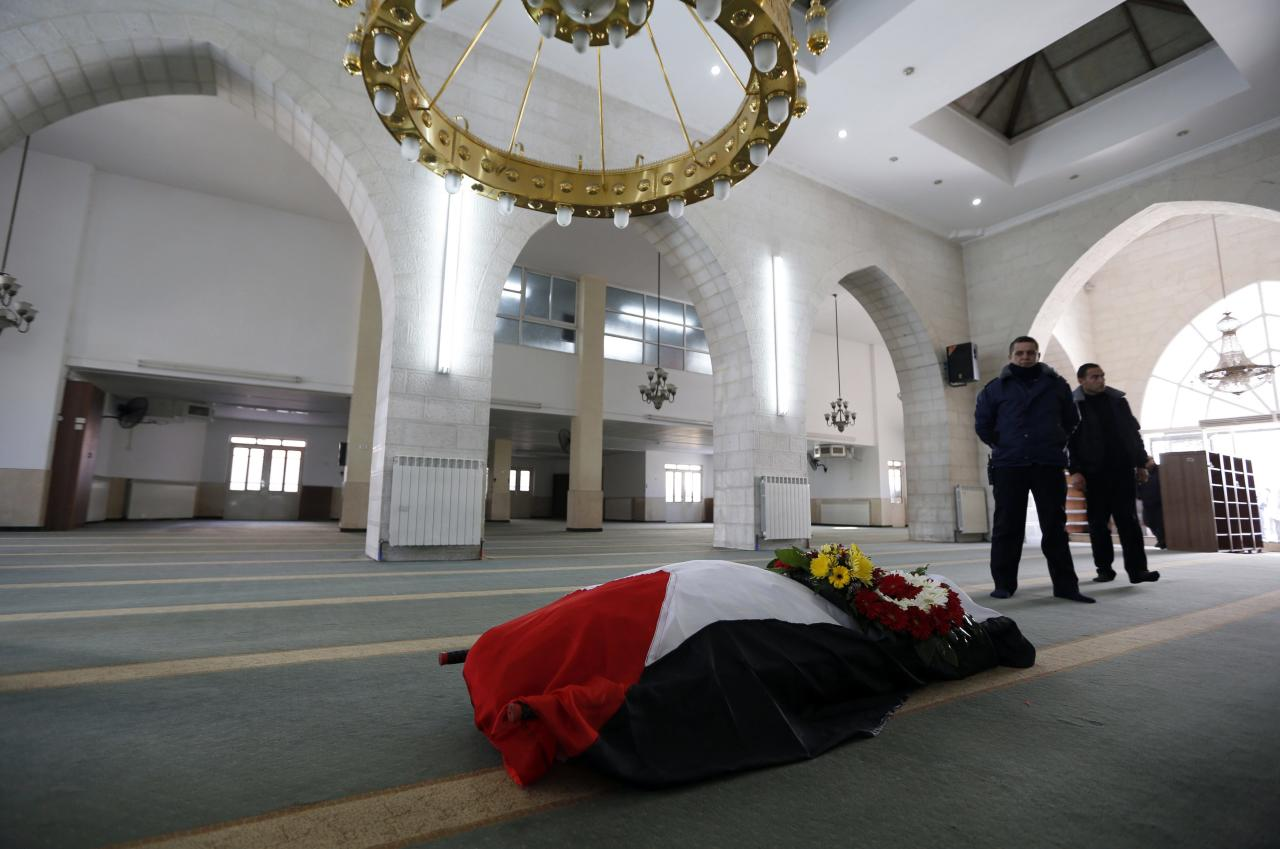 The flag-covered body of Palestinian ambassador to Prague, Jamal al-Jamal lies in a mosque during his funeral in the West Bank city of Ramallah January 8, 2014. Al-Jamal died on January 1 in a mysterious explosion after opening a safe in his residence at the Palestinian mission in Prague. REUTERS/Mohamad Torokman (WEST BANK - Tags: POLITICS OBITUARY)