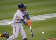 Houston Astros' Yuli Gurriel hits a single against the Oakland Athletics during the second inning of a baseball game Friday, April 2, 2021, in Oakland, Calif. (AP Photo/Tony Avelar)