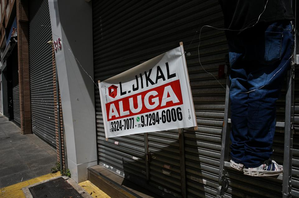 SAO PAULO, BRAZIL - MARCH 08: A man posts a 'For Lease' sign in front of a shuttered shop in downtown during the first business day after the state of Sao Paulo declared the most restrictive