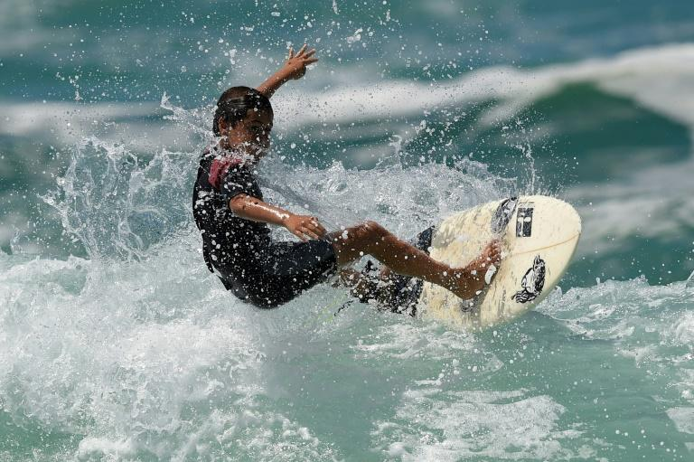Young surfer Rickson Falcao, 10, rides a wave at Saquarema's beach in Rio de Janeiro state, Brazil, on November 29, 2017