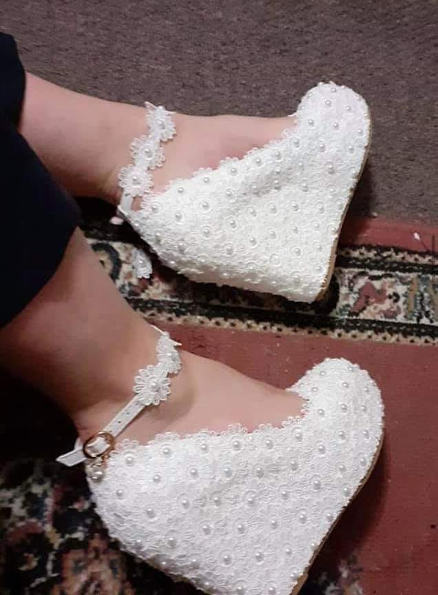 Image of bride wearingwhite wedding wedge heels with lace and beaded materiel, scoop open front and lacy beaded strap that have divided opinions online.