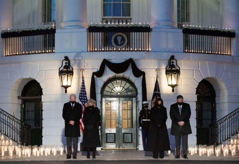 US President Joe Biden, First Lady Jill Biden, US Vice President Kamala Harris and her husband, Doug Emhoff, hold a moment of silence during a candelight ceremony in honor of those who lost their lives to Coronavirus on the South Lawn of the White House in Washington, DC, February 22, 2021.