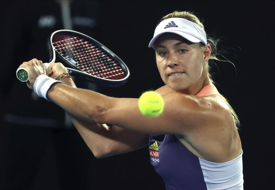Germany's Angelique Kerber makes a backhand return to Italy's Elisabetta Cocciaretto during their first round singles match at the Australian Open tennis championship in Melbourne, Australia, Tuesday, Jan. 21, 2020. (AP Photo/Lee Jin-man)
