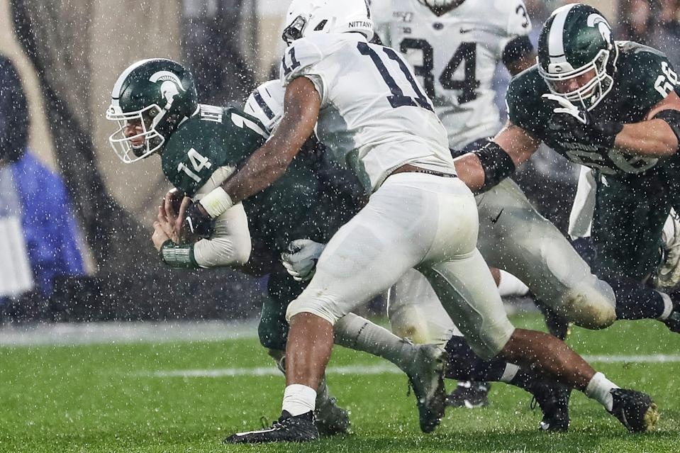 Michigan State quarterback Brian Lewerke keeps the ball for a run and is stopped by Penn State linebacker Micah Parsons (11) during the second half at Spartan Stadium in East Lansing, Saturday, October 26, 2019.