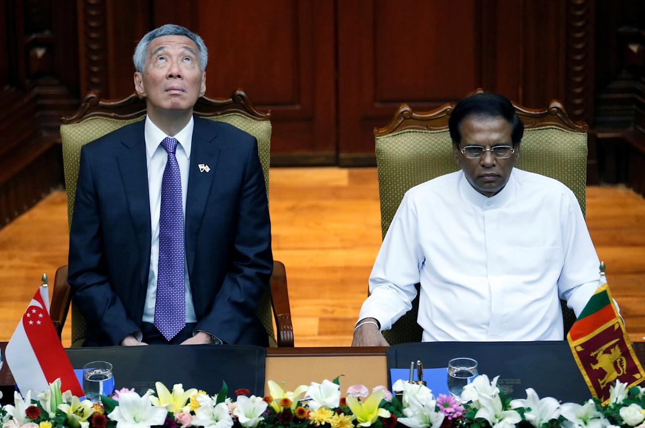 Singapore Prime Minister Lee Hsien Loong (L) looks up next to the Sri Lankan President Maithripala Sirisena in Colombo, Sri Lanka January 23, 2018. REUTERS/Dinuka Liyanawatte