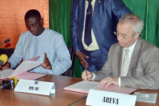 Niger Minister for Mining Omar Hamidou Tchiana (L) and Chairman of the board of directors for French energy company Areva, Luc Oursel (R), sign an agreement on May 26, 2014 in Niamey
