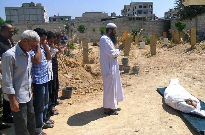 In this citizen journalism image provided by the United media office of Arbeen which has been authenticated based on its contents and other AP reporting, Syrians pray during the funeral of a man killed from a shell in Arbeen town, a suburb of Damascus, Syria, Tuesday, Sept. 3, 2013. (AP Photo/United media office of Arbeen)