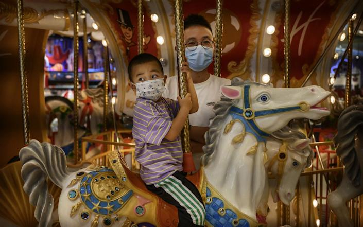 A Chinese boy and his father wear protective masks on a ride while shopping at a toy store in Beijing - Getty