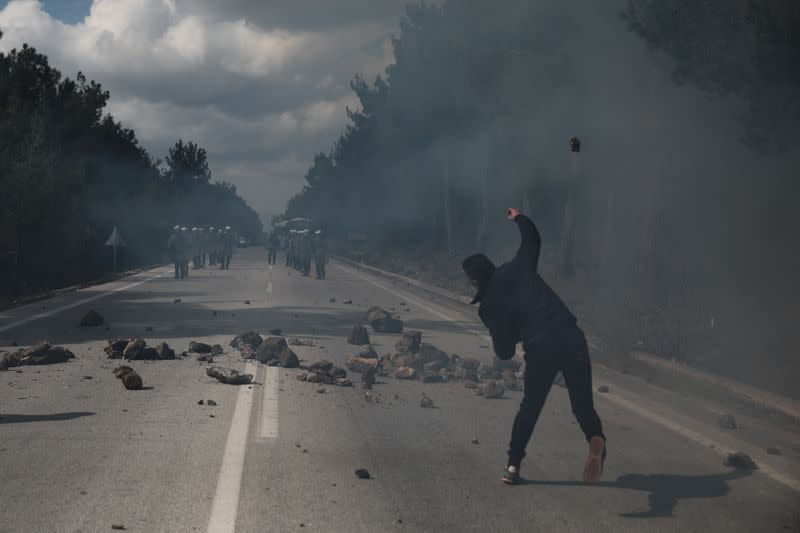 A demonstrator, who opposes the building of a new closed migrant detention centre, throws a rock at riot police during clashes, in the area of Diavolorema on the island of Lesbos