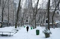 A person walks through Bryant Park on December 17, 2020 in New York, the morning after a powerful winter storm hit US northeastern states