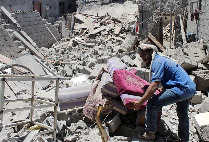 A Yemeni man searches for survivors under the rubble in houses destroyed by an overnight Saudi-led air strike on a residential area in the port city of Aden's Dar Saad suburb, on May 2, 2015