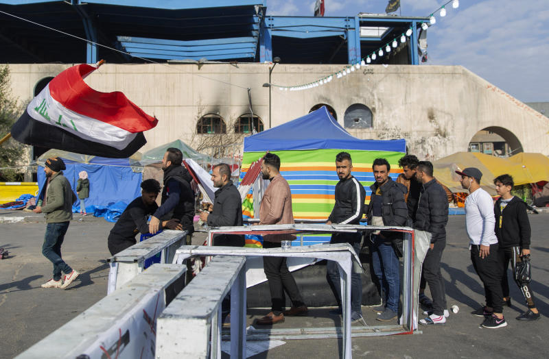 Protesters go through security inspection as they arrive to Tahrir Square, during ongoing protests, in Baghdad, Iraq, Wednesday, Dec. 25, 2019. (AP Photo/Nasser Nasser)