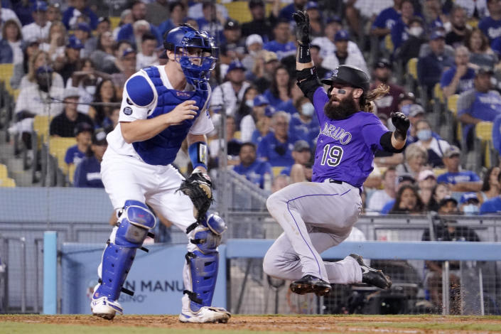 Colorado Rockies' Charlie Blackmon, right, scores on a single by Ryan McMahon as Los Angeles Dodgers catcher Will Smith waits for the ball during the eighth inning of a baseball game Friday, July 23, 2021, in Los Angeles. (AP Photo/Mark J. Terrill)