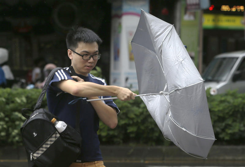 A man struggles with his umbrella against powerful gusts of wind generated by typhoon Ineng in Taipei, Taiwan, Saturday, Aug. 24, 2019. (AP Photo/Chiang Ying-ying)