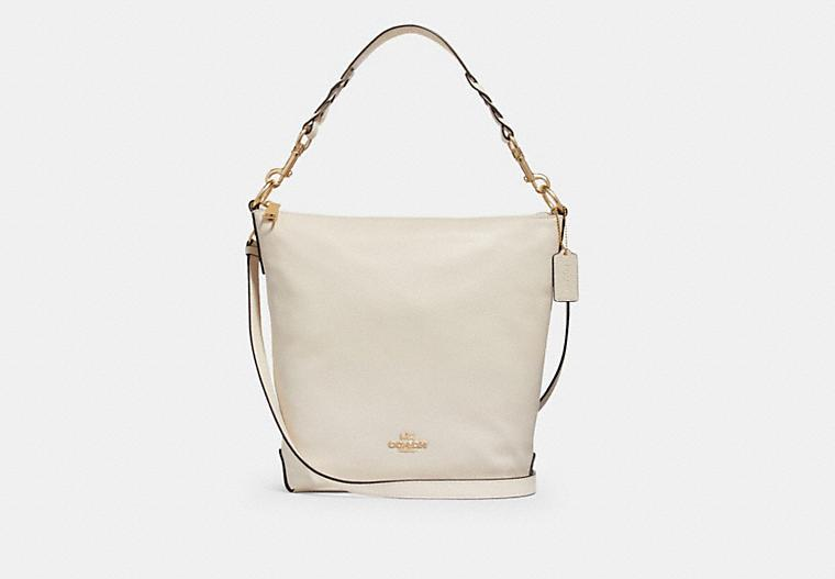 Product photo of the Abby Duffle shoulder bag in beige with gold hardware. Image via Coach Outlet.