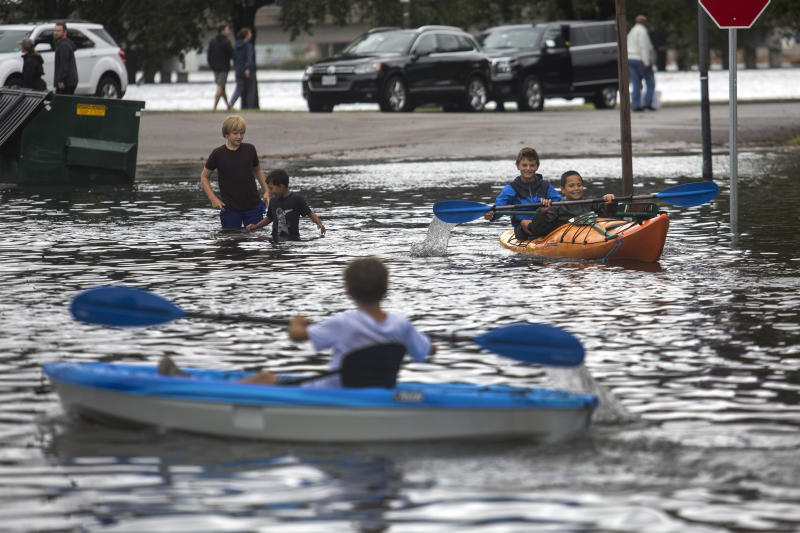 Kids kayak through the flooded streets near the corner of Mowbray Arch and Botetourt Street after the storms caused by Hurricane Dorian on Friday, Sept. 6, 2019, in Norfolk, Va. (Sarah Holm/The Virginian-Pilot via AP)