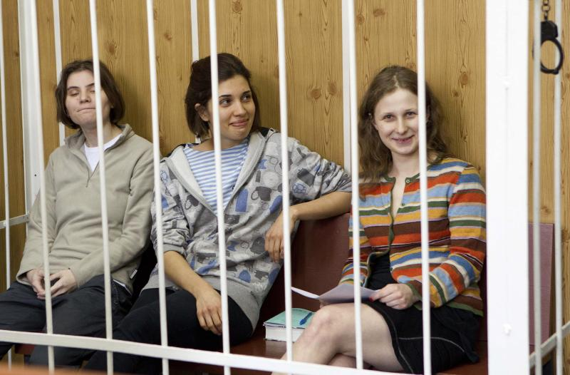 """From left, Yekaterina Samutsevich, Nadezhda Tolokonnikova, Maria Alekhina, members of feminist punk group Pussy Riot sit behind bars at a court room in Moscow, Russia, Friday, July 20, 2012. The trial of feminist punk rockers who chanted a """"punk prayer"""" against President Vladimir Putin from a pulpit inside Russia's largest cathedral started in Moscow on Friday amid controversy over the prank that divided devout believers, Kremlin critics and ordinary Russians. (AP Photo/Misha Japaridze)"""