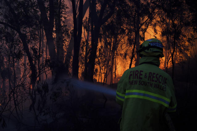 Fire and Rescue NSW firefighters conduct property protection as a bushfire burns close to homes on Railway Parade in Woodford NSW, Friday, Nov. 8, 2019. Firefighters battled 90 fires across Australia's most populous state, New South Wales, with the most intense in the northeast where flames have been fanned by strong winds, Rural Fire Service Commissioner Shane Fitzsimmons said. (Dan Himbrechts/AAP Image via AP)