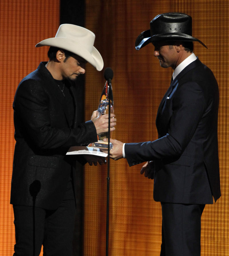 ** CORRECTS TO 44TH ANNUAL COUNTRY MUSIC AWARDS STED 43RD ** Brad Paisley, left, accepts the Entertainer of the Year Award from Tim McGraw at the 44th Annual Country Music Awards in Nashville, Tenn., Wednesday, Nov. 10, 2010. (AP Photo/Mark Humphrey)