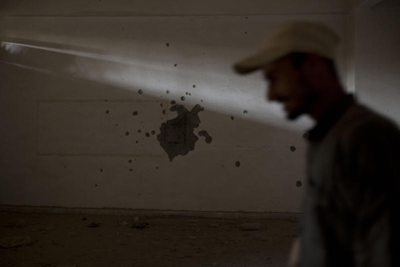 In this Thursday, Sept. 5, 2019, photo, a guard walks through the room where Islamic State militants executed their prisoners in a sprawling, makeshift prison in the basement of the stadium in Raqqa, Syria. Two years after the military offensive to oust IS from its stronghold, Raqqa has been picking up the pieces. (AP Photo/Maya Alleruzzo)